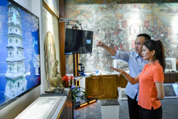 游客在工作人员的指导下通过LM体感互动展示系统观看飞虹塔全貌