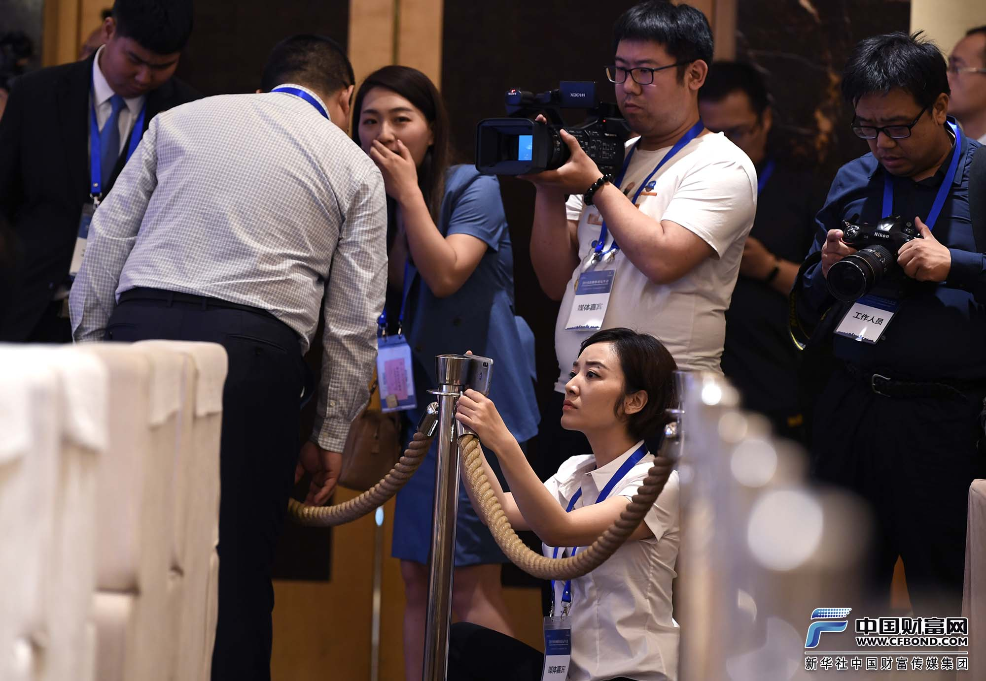 中国财富网记者张静静在金融街论坛年会现场手机采访拍摄