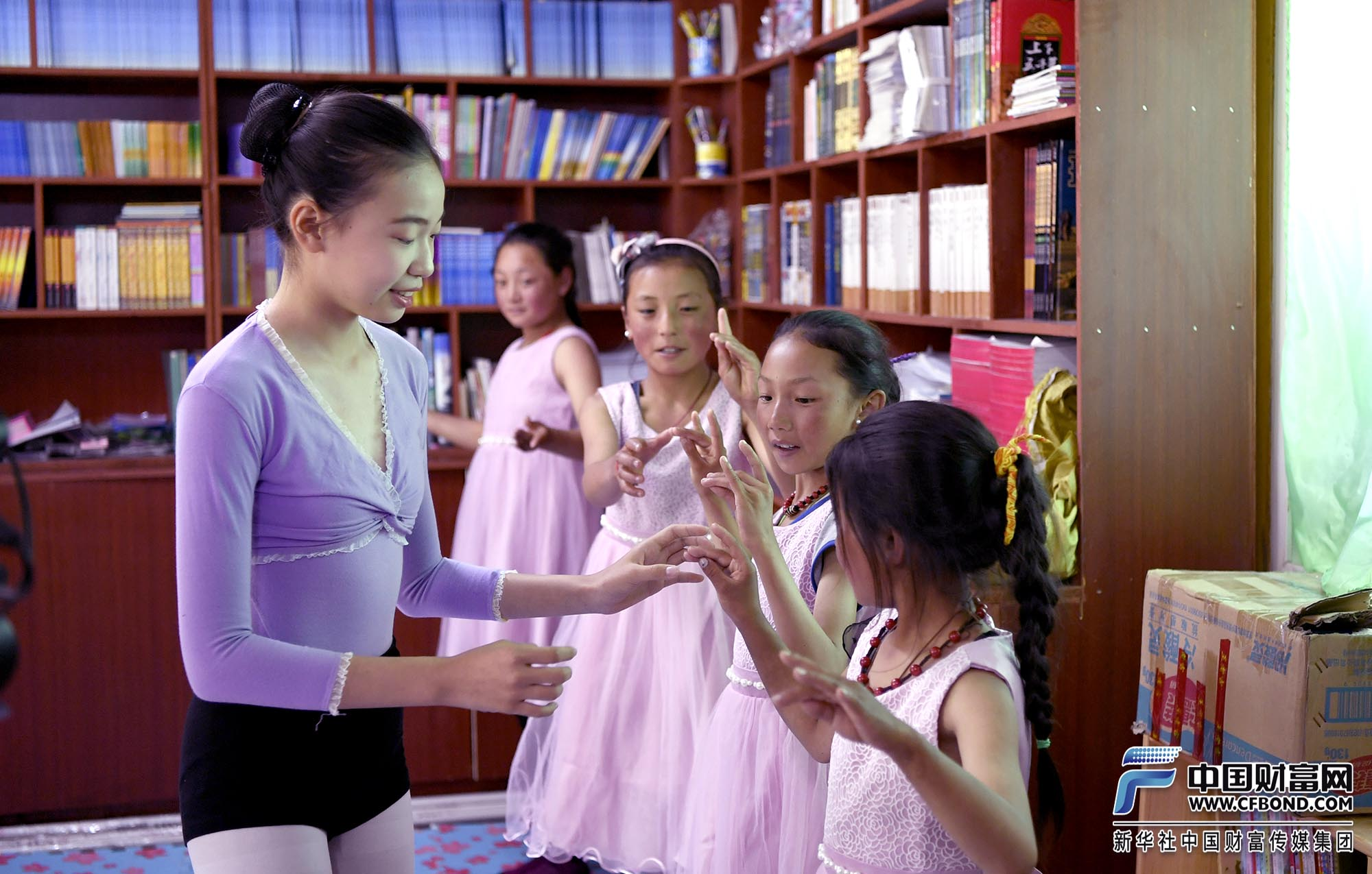 小舞蹈老师在教孩子们芭蕾舞动作